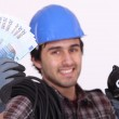 Construction worker with bills and piggy bank in hands — Stock Photo #8164246