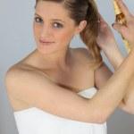 Blond woman using hair spray — Stock Photo #8165300