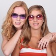 Studio shot of two pretty teenagers wearing colored sunglasses — Stock Photo #8165981