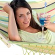 Woman having a cocktail drink in a hammock — Stock Photo