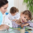 Teacher helping pupil with her school work — Stockfoto #8166280