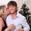 Young woman kissing her boyfriend at Christmas — Stockfoto