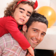 Stock Photo: Father giving dressed as devil a piggy-back