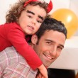 Father giving dressed as devil a piggy-back — Stock Photo