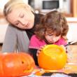 Mother and daughter preparing pumpkin in kitchen — Stock Photo