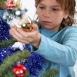 Stock Photo: Little boy decorating Christmas tree
