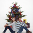 Couple sitting in front of their Christmas tree — Stock Photo