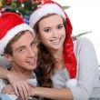 Couple in front of Christmas tree — Stockfoto