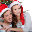 Couple in front of Christmas tree - Stock Photo