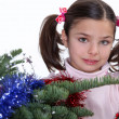 Young girl decorating a Christmas tree — Foto Stock