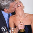 Couple popping a champagne cork — Stock Photo