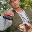 Huntsman posing with dog outdoors - Stock Photo