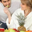 Stock Photo: Young couple eating fruit at breakfast