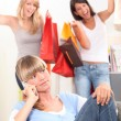 Stock Photo: Young womon telephone as her friends walk in with bags of retail pur