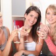 Three female friends drinking wine on sofa — Stock Photo