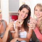 Three female friends drinking wine on sofa — Stock Photo
