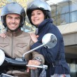 Couple riding on scooter — Stockfoto