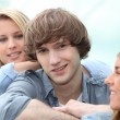 Three smiling teenagers sitting together — Stock Photo