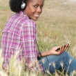 Womlistening to music in field — Stock Photo #8168931