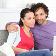 Stock Photo: Young metis couple doing computer on the couch