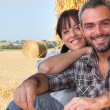 Stock Photo: Farming couple sat by hay