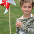 Stock Photo: Little girl and a paper windmill