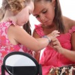Foto Stock: Girls putting on jewellery