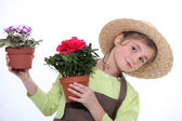 9 years old girl dressed in horticulturist taking flower pots — Stok fotoğraf