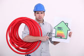 Grumpy man giving a property an energy efficiency rating of G — Stock Photo