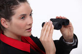 Suspicious woman watching through binoculars — Stock Photo