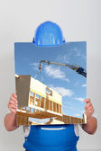 Faceless worker showing a building site picture — Stock Photo