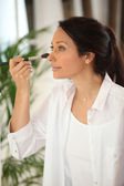 Woman applying blush — Stock Photo