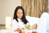 Woman reading a magazine over breakfast — Stock Photo