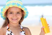 Girl holding sun-cream — Stock Photo