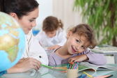 Teacher helping a pupil with her school work — Stock Photo