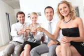 Two couple sitting holding up champagne glasses — Stock Photo