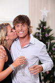 Young woman kissing her boyfriend at Christmas — Stock Photo