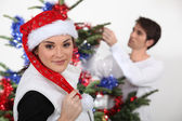 Woman with Christmas cap and man decorating fir — Stock Photo