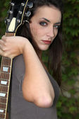 Dark hair woman holding a guitar looked mysterious — Stock Photo