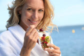 Portrait of a woman eating fruit salad — Stock Photo