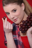 Attractive woman eating grapes — Stock Photo
