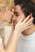 A woman takes her boyfriend's face in her hands — Stock Photo
