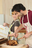 Couple cooking roast chicken — Stock Photo