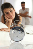 Couple staring at an alarm clock — Stock Photo