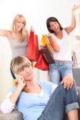 Young woman on the telephone as her friends walk in with bags of retail pur — Stock Photo