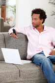 Young man relaxing on the sofa and sending text message with his cell phone — Stock Photo
