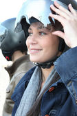 A woman turning up her motorcycle helmet visor — Stock Photo