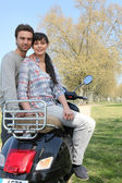 Couple in the park with their scooter — Stock Photo
