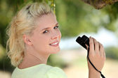 Young fair-haired woman with binoculars — Stock Photo