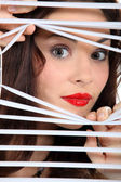 Woman looking through window blinds — Stock Photo